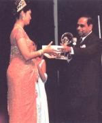 Plaque presentation, Dharmatma Saran, Chief Organizer presenting a plaque & a check for $3000 to outgoing queen Santripti Vellody